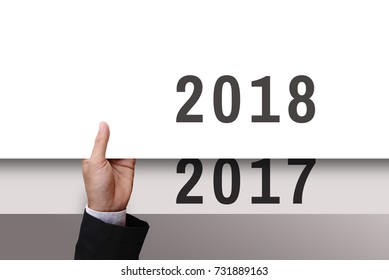 Businessman's hand holding from under of white cardboard or paper new year 2018 replace old year 2017.