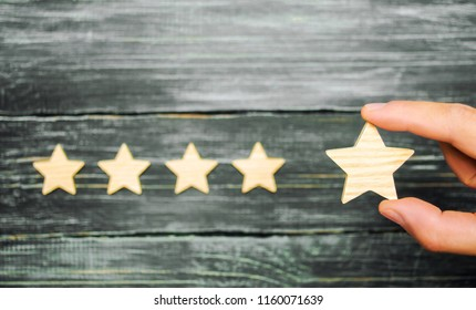 The businessman's hand holds the fifth star. A new star, achievement.The concept of the rating of hotels and restaurants, the evaluation of critics and visitors. Quality level, good service.