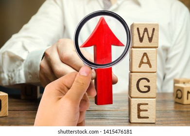 Businessman's hand holds red arrow up near wooden blocks with word Wage. Salary increase concept. Wages rate. Revenue growth and profits. Successful business. Career rise. Promote. Stability