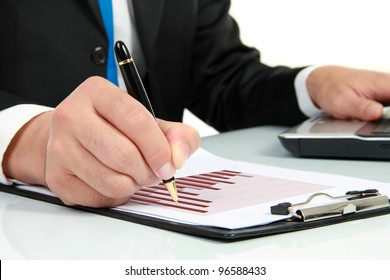 Businessman's hand looking at diagram on financial report