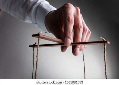 A Businessman's Hand Manipulating Marionette With String Against Gray Background