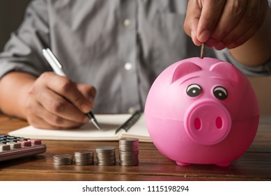 Businessman's hand is picking for coin up to drop into a piggy bank - Concept of saving money for the future