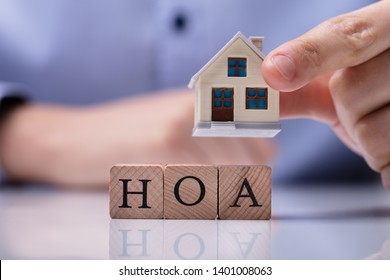 Businessman's Hand Placing House Models On Wooden HOA Cubic Blocks Over Desk