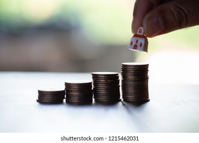 Businessman's  hand placing small house model on increasing golden stacked coins.