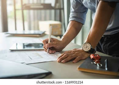 Businessman's hand pointing at business document during discussion at his working place in office.