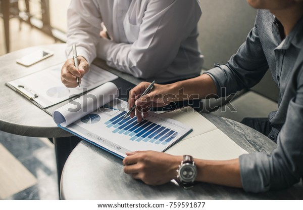 Businessman's hand pointing at business document during discussion at meeting.