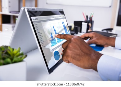 Businessman's Hand Pointing On Laptop Screen Showing Graph Over The Desk