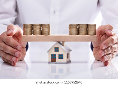 Businessman's Hand Protecting Stacked Coins On Seesaw With House Model