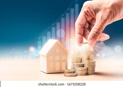 Businessman's hand putting coins in stack near home model with graph background. Finance or Savings home concept