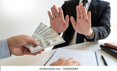 Businessman's Hand Refusing To Take Bribe cash banknote from business partner, anti-corruption and venalityconcept