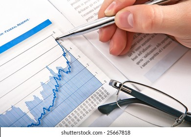 Businessman's hand showing diagram on financial report with pen. Business background 02