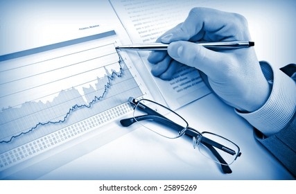 Businessman's hand showing diagram on financial report with pen. Business background blue