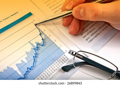 Businessman's hand showing diagram on financial report with pen. Business background 08