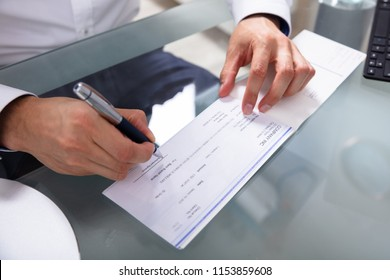 Businessman's Hand Signing Cheque On Glass Desk