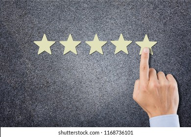 The businessman's hand in the suit holds the fifth star. Get the fifth star. The concept of the rating of hotels and restaurants, the evaluation of critics and visitors. Quality level, good service.