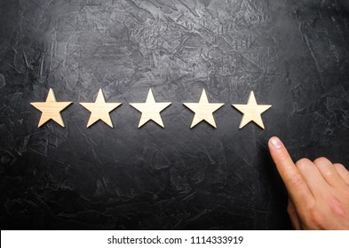 The businessman's hand in the suit points to the fifth star. Get the fifth star. The concept of the rating of hotels and restaurants, evaluation of critics and visitors. Quality level, good service.