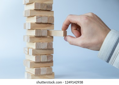Businessman's hand taking the first block or putting the last block to a sturdy tower of wooden blocks. Concept photo of planning, taking risks and strategizing. Light gray background.