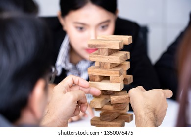 Businessman's hand is trying to hold a tower of wooden blocks game, Alternative risk and strategy in business concept