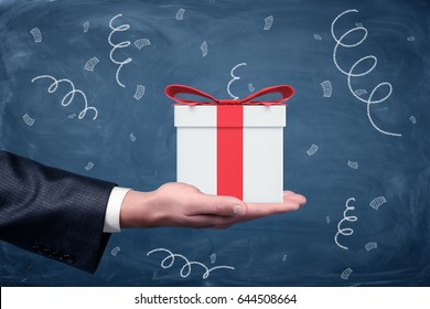 A businessman's hand turned up and a small gift box with a red bow standing on chalkboard background. Promotions and bonuses. Getting clients interested. Best offers.