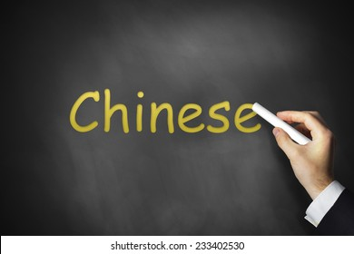 businessmans hand writing chinese on black chalkboard