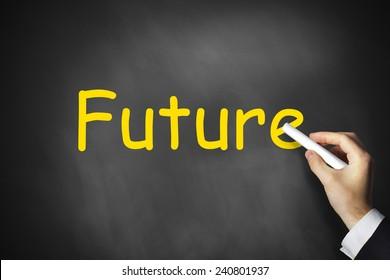businessmans hand writing future on black chalkboard