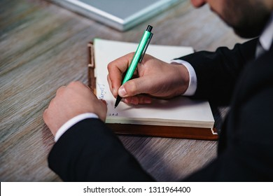 Businessman's Hand Writing Something Down In A Notebook. Close Up Of Man's Hand In Suit Writing On Notebook Or Document.