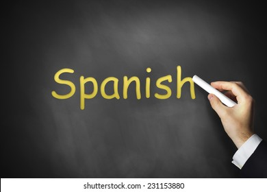 businessmans hand writing spanish on black chalkboard