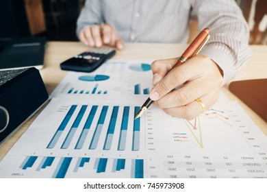 Businessman's hands with calculator at the office and Financial data analyzing counting on report business