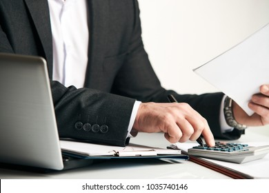 Businessman's hands using calculator and Financial data analyzing on white desk at the office, close-up