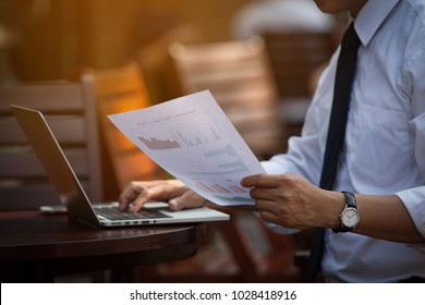 Businessman's Key Research And AUDIT Income Statement DATA from Excel Spreadsheets. Audit Making Database Report Financial Planning Report In a CAFE in Park Near the Office Before Entering Meeting