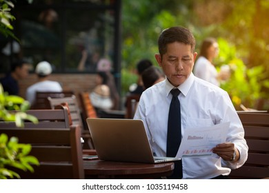 Businessman's key research and audit income statement data from Excel spreadsheets. audit making database report financial planning report In a cafe in a park .Commitment and commitment to success.