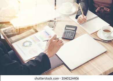 Businessman's key research and audit income statement data from Excel spreadsheets. audit making database financial planning report In a cafe.business team partner meeting concept