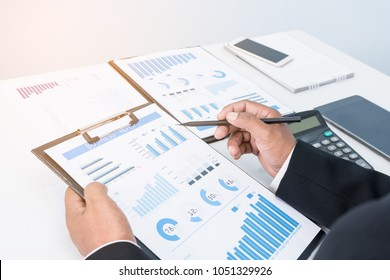 Businessman's key research and audit income statement data from Excel spreadsheets.audit making database report financial planning report In a cafe in a park near the office .businessmeeting concept
