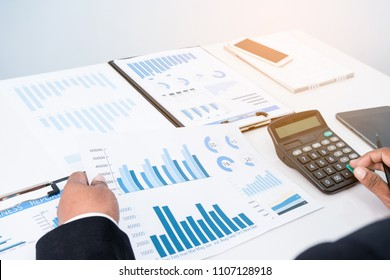 Businessman's key research and audit income statement data from Excel spreadsheets. audit making database report financial planning report before entering the meeting in the afternoon.