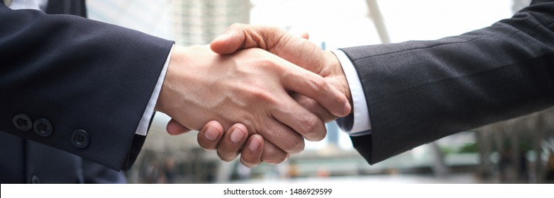 Businessman's making handshake. Negotiation meeting for a successful merger. Business etiquette for greeting and congratulation each other. Crop only the hand part in a panoramic view.