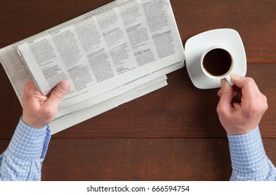 Businessman's morning: unrecognizable man reading morning newspapers and drinking coffee; upper viewpoint