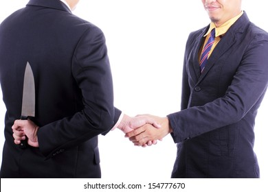 Businessmans shake hand after discussed while another people holding knife for double-cross