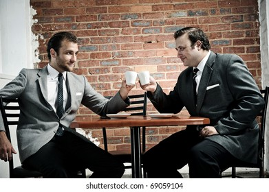 businessmen agree as the cheers with their coffee mugs
