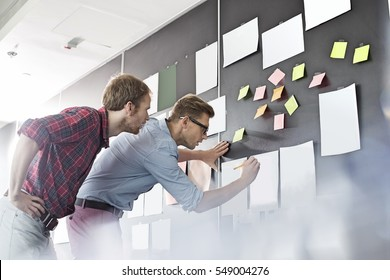 Businessmen analyzing documents on wall in office