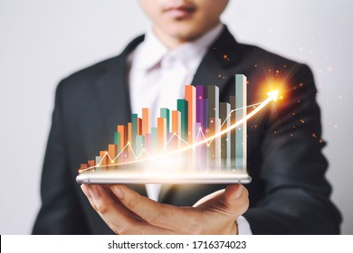 Businessmen Asia  holding Smartphone and showing a growing virtual hologram of statistics, graph and chart with arrow up on white background. Stock market. Business growth, planing concept.