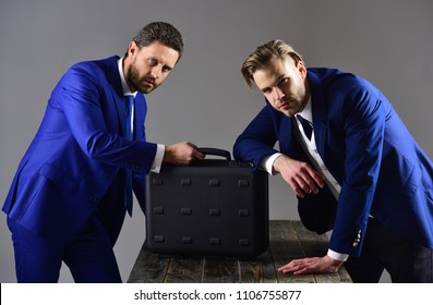 Businessmen with black briefcase on dark background. Men in suit or business partners with serious faces meet for deal. Business deal concept. Handover of briefcase with illegal goods or bribe.