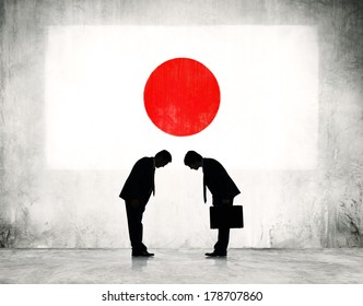 Businessmen Bowing at Japanese Flag