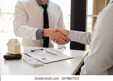 Businessmen and brokers real estate agents catch hand after completing negotiations to buy houses insurance and sign contracts. Home insurance concept.