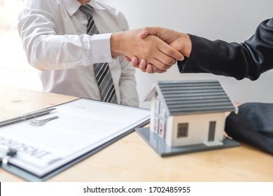 Businessmen and brokers real estate agents shake hand after completing negotiations to buy houses insurance and sign contracts. Home insurance concept.