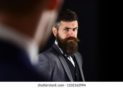 Businessmen, business partners meeting on black background. Businessmen look at each other with judgment, copy space. Eye contact concept. Business partners on serious faces stand opposite each other.