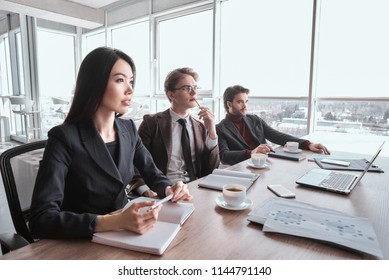 Businessmen and businesswoman at office working together sitting at table having conference with boss listening concentrated