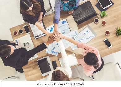 Businessmen and businesswomen joining hands in group meeting at multicultural office room showing teamwork, support and unity in business. Diversity workplace and corporate people working concept.