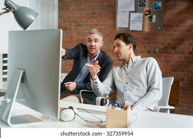 Businessmen and businesswomen working over computer in busy office