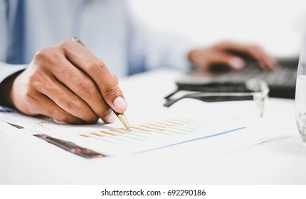 Businessmen are busy their work on paper and on the computer screen his.