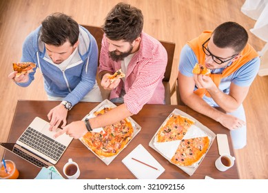 Businessmen in casual style use computers in office and eat pizza